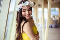 有长的头发的美丽的少妇在一个夏日 黄色礼服的女傧相在海餐馆 免版税库存照片
