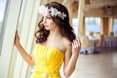 有长的头发的美丽的少妇在一个夏日 黄色礼服的女傧相在海餐馆 免版税库存图片