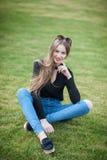 有长的头发的美丽的少妇坐绿草 免版税库存照片