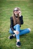 有长的头发的美丽的少妇坐绿草 免版税库存图片