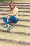 有长的头发的美丽的性感的女孩坐台阶哀伤在牛仔裤和衬衣 免版税库存图片