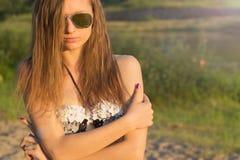 有长的头发的美丽的性感的女孩有在晴朗的温暖的天海滩的被晒黑的皮肤佩带的太阳镜的  免版税库存图片