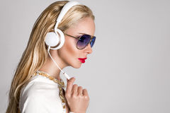 有长的头发的美丽的性感的白肤金发的妇女和坐与耳机的一套典雅的白色衣服的完善的身体 免版税库存图片