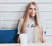 有长的头发的美丽的时兴的白肤金发的女孩在与一杯咖啡的一个咖啡馆休息 木背景 Instagram 免版税库存图片