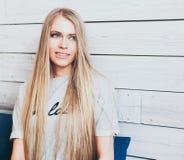 有长的头发的美丽的时兴的白肤金发的女孩在看窗口的咖啡馆休息 免版税库存图片