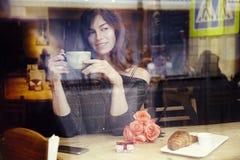 有长的头发的美丽的白种人妇女在咖啡馆,庆祝,当前箱子和玫瑰色花的窗口附近 St华伦泰` s天conce 免版税库存照片
