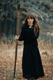 有长的头发的美丽的神奇神秘的女孩在拿着一条辫子的黑礼服在途中的黑暗的秋天森林里 神秘俏丽 免版税库存图片