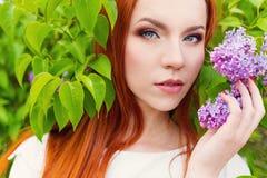 有长的头发的美丽的逗人喜爱的性感的红发女孩在有丁香花束的一件白色礼服在手上  免版税库存照片