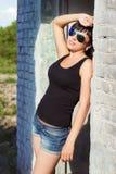 有长的头发的美丽的年轻性感的女孩在一个晴朗的夏日简而言之站立在太阳镜的新鲜空气的临近白色砖 图库摄影