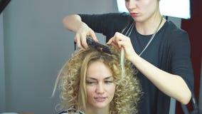 有长的头发的美丽,白肤金发的头发的女孩,美发师做在美容院的非洲卷毛 专业护发 股票录像