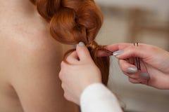 有长的头发的美丽,红发女孩,美发师编织法国辫子,在美容院 图库摄影