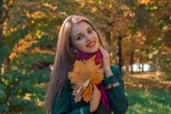 有长的头发的逗人喜爱的女孩在公园在手和微笑保留槭树叶子 免版税图库摄影