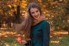 有长的头发的逗人喜爱的女孩在公园站立并且保持苹果计算机手中 免版税库存图片