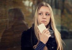 有长的头发的青少年的女孩有电话的 免版税库存照片