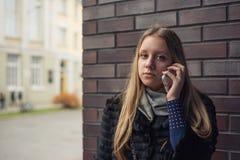 有长的头发的青少年的女孩谈话在电话户外在外套 免版税库存照片