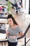有长的直发的年轻可爱的女商人举行一次笔记本或工作面试在咖啡商店或咖啡馆 免版税库存图片