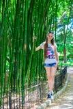 有长的头发的年轻和微笑的女孩在高竹子附近站立 免版税库存照片