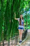 有长的头发的年轻和微笑的女孩在高竹子附近站立 免版税图库摄影