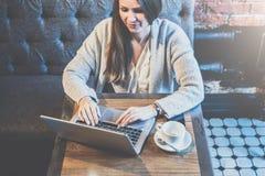 有长的头发的年轻女实业家坐在咖啡馆的桌上并且使用膝上型计算机 在桌上是咖啡 图库摄影