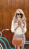 有长的头发的年轻性感的白肤金发的女孩有在站立近的葡萄酒绿色自行车和拿着杯子o的太阳镜的棕色葡萄酒袋子的 库存照片