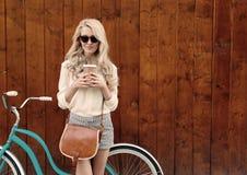 有长的头发的年轻性感的白肤金发的女孩有在站立近的葡萄酒绿色自行车和拿着杯子o的太阳镜的棕色葡萄酒袋子的 图库摄影