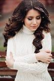 有长的黑发的年轻美丽和非常时髦的女孩在一件长期被编织的白色礼服摆在 时尚画象性感 库存图片