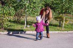 有长的头发的年轻美丽的女孩在夹克母亲在晴朗的d教他的女儿走他们的婴孩的第一步户外 库存图片