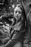 有长的头发的年轻美丽的少年女孩在衬衣和牛仔布在L短缺基于树在步行期间在公园Striysky 免版税库存图片