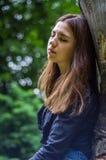有长的头发的年轻美丽的少年女孩在衬衣和牛仔布在L短缺基于树在步行期间在公园Striysky 库存图片