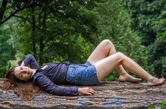 有长的头发的年轻美丽的少年女孩在衬衣和牛仔布在L短缺基于树在步行期间在公园Striysky 免版税图库摄影