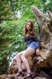 有长的头发的年轻美丽的少年女孩在衬衣和牛仔布在L短缺基于树在步行期间在公园Striysky 免版税库存照片