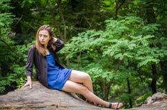 有长的头发的年轻美丽的少年女孩在衬衣和牛仔布在L短缺基于树在步行期间在公园Striysky 库存照片
