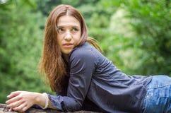 有长的头发的年轻美丽的少年女孩在衬衣和牛仔布在L短缺基于树在步行期间在公园Striysky 图库摄影