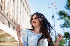 有长的头发的画象美丽的女孩在偶然成套装备在城市走 美丽的深色的whith咖啡 免版税库存图片