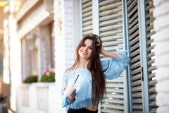 有长的头发的画象美丽的女孩在摆在意大利咖啡馆的偶然成套装备 美丽的浅黑肤色的男人保留咖啡 免版税库存图片