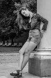 有长的头发的年轻逗人喜爱的女孩在衬衣和牛仔布在公园短缺走在摆在c附近的利沃夫州Striysky晴朗的夏日 库存图片