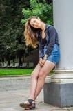 有长的头发的年轻逗人喜爱的女孩在衬衣和牛仔布在公园短缺走在摆在c附近的利沃夫州Striysky晴朗的夏日 图库摄影