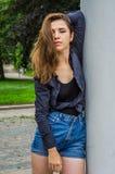 有长的头发的年轻逗人喜爱的女孩在衬衣和牛仔布在公园短缺走在摆在c附近的利沃夫州Striysky晴朗的夏日 免版税库存照片