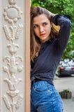 有长的头发的年轻逗人喜爱的女孩在衬衣和牛仔布在公园短缺走在摆在c附近的利沃夫州Striysky晴朗的夏日 库存照片