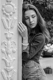 有长的头发的年轻逗人喜爱的女孩在衬衣和牛仔布在公园短缺走在摆在c附近的利沃夫州Striysky晴朗的夏日 免版税库存图片