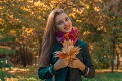 有长的头发的年轻逗人喜爱的女孩是微笑和拿着叶子 图库摄影