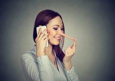 有长的鼻子的愉快的少妇谈话在手机 免版税库存图片