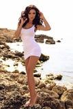 有长的黑暗的卷发佩带的比基尼泳装和海滩分类的性感的妇女 免版税图库摄影