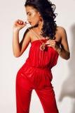 有长的黑暗的卷发的被晒黑的妇女穿着有珠宝的典雅的红色衣服 免版税库存照片