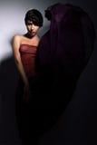 有长的黑暗的紫色裙子的俏丽的妇女 免版税库存图片