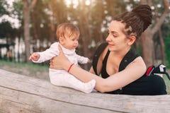 有长的dreadlock头发举行的一名美丽的微笑的年轻深色的妇女一个俏丽的婴孩 母亲体贴看孩子 免版税库存照片