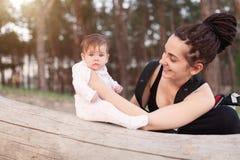 有长的dreadlock头发举行的一名美丽的微笑的年轻深色的妇女一个俏丽的婴孩 免版税库存图片