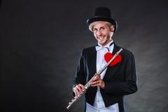 有长笛和心脏的男性长笛演奏家 爱曲调 库存照片