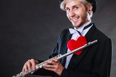 有长笛和心脏的男性长笛演奏家 爱曲调 图库摄影