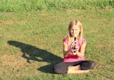 有长笛的微笑的女孩 库存图片